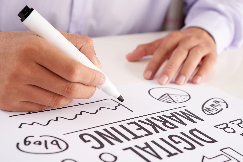 crop-hands-making-notes-on-digital-marketing