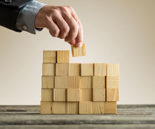 businessman-building-a-structure-with-wooden-cubes