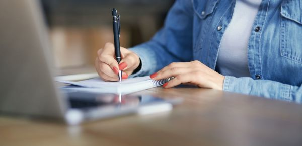woman-holding-pen-and-writing